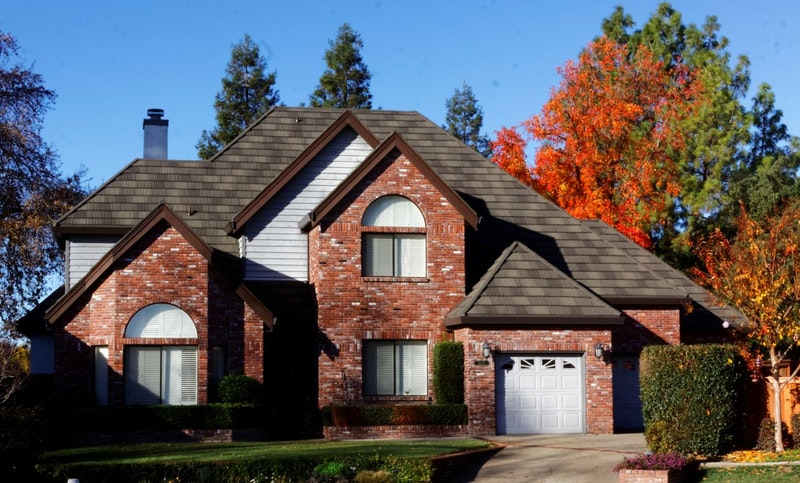 Suburban home with brick and light blue vinyl siding and Tilcor metal roof tiles in Ironstone.