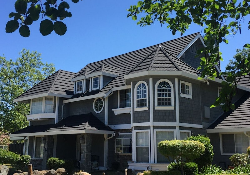 Shake siding home with Tilcor metal roof tiles in Black Iron.