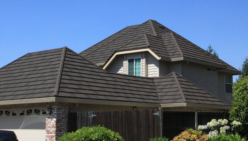 Brick and vinyl siding home with Tilcor metal roof tiles in Black Iron.