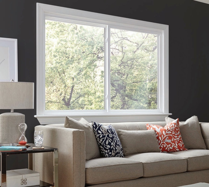 Large white vinyl sliding window with prominent sill in a gray walled living room with a tan couch and colorful pillows.
