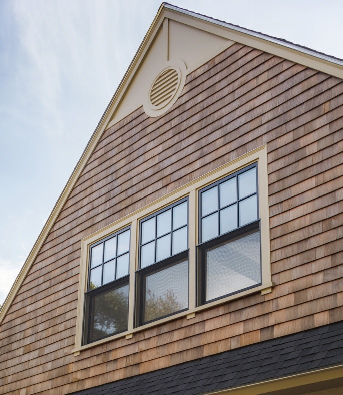 Exterior view of a home with jeld-wen premium vinyl double hung windows in black with colonial grids on top sashes.