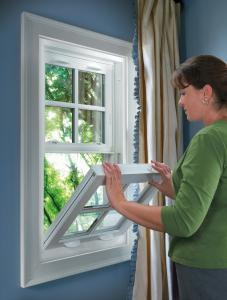 Woman opening a single or double hung window with a tilt in sash with colonial grilles.