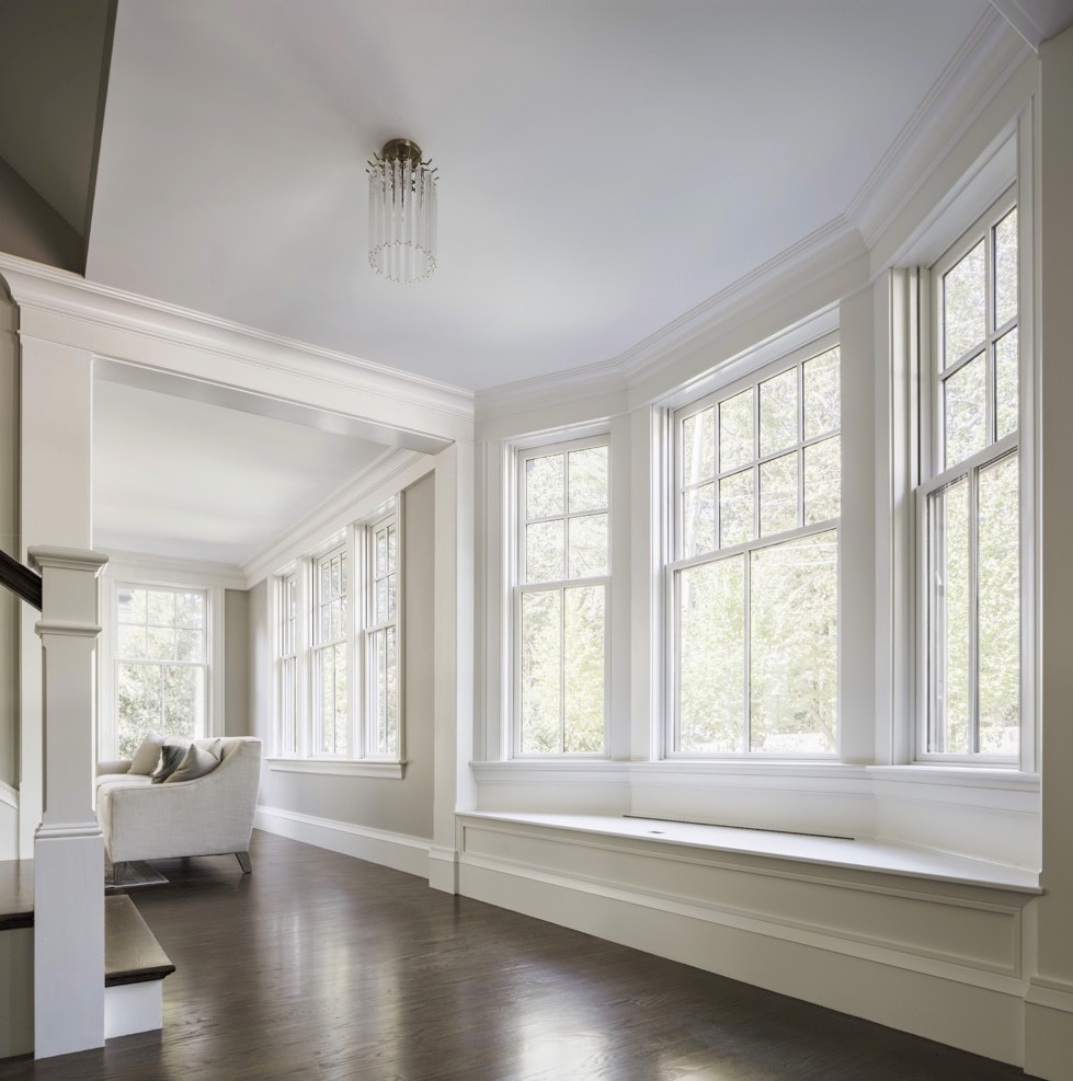 Interior of a foyer and stairs and white three lite, single-hung bay windows with grids.