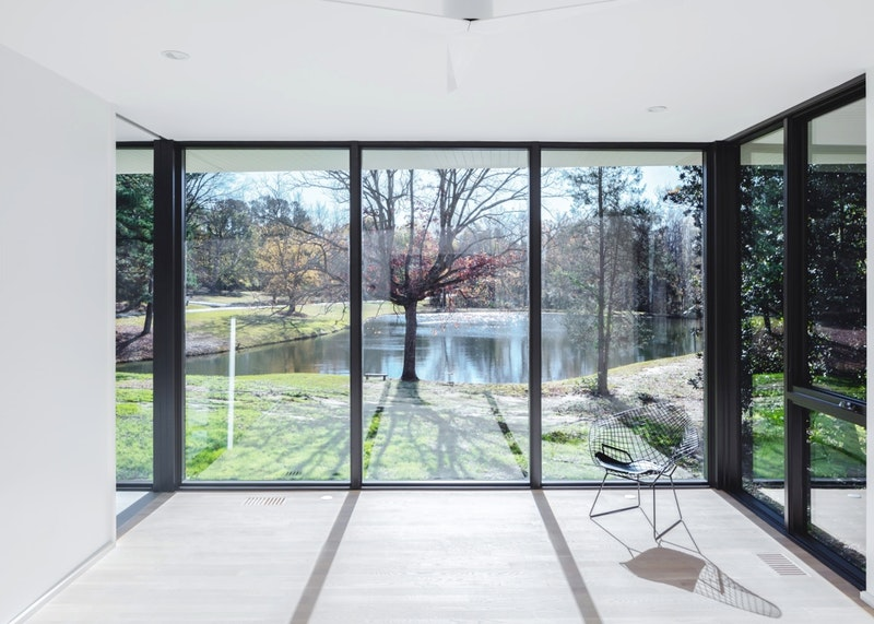 Three large dark frames of Jeld-Wen premium vinyl picture windows in a home. The windows overlook a backyard and pond.