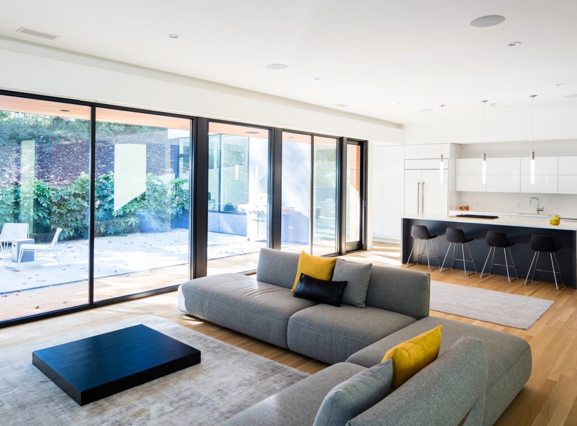 Several large Jeld-Wen picture windows with black frames in a modern living room. The windows are floor to ceiling.
