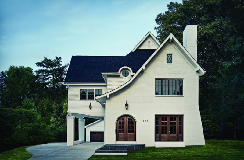 White brick home with natural wood doors and several double-hung, picture and round windows.