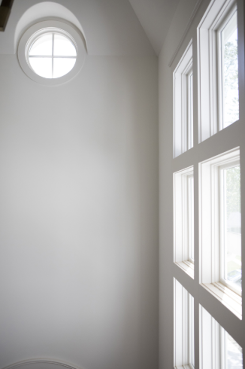Interior wall with a small fixed round window placed near the ceiling.
