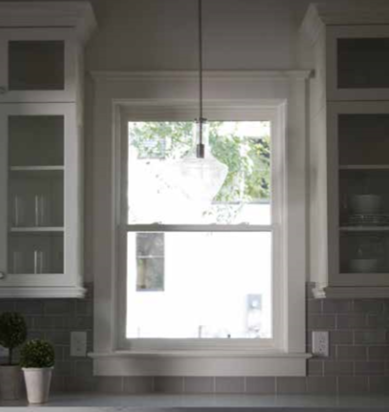 View of a kitchen with grey subway tile backsplash, and accent drop light, and white cabinets.