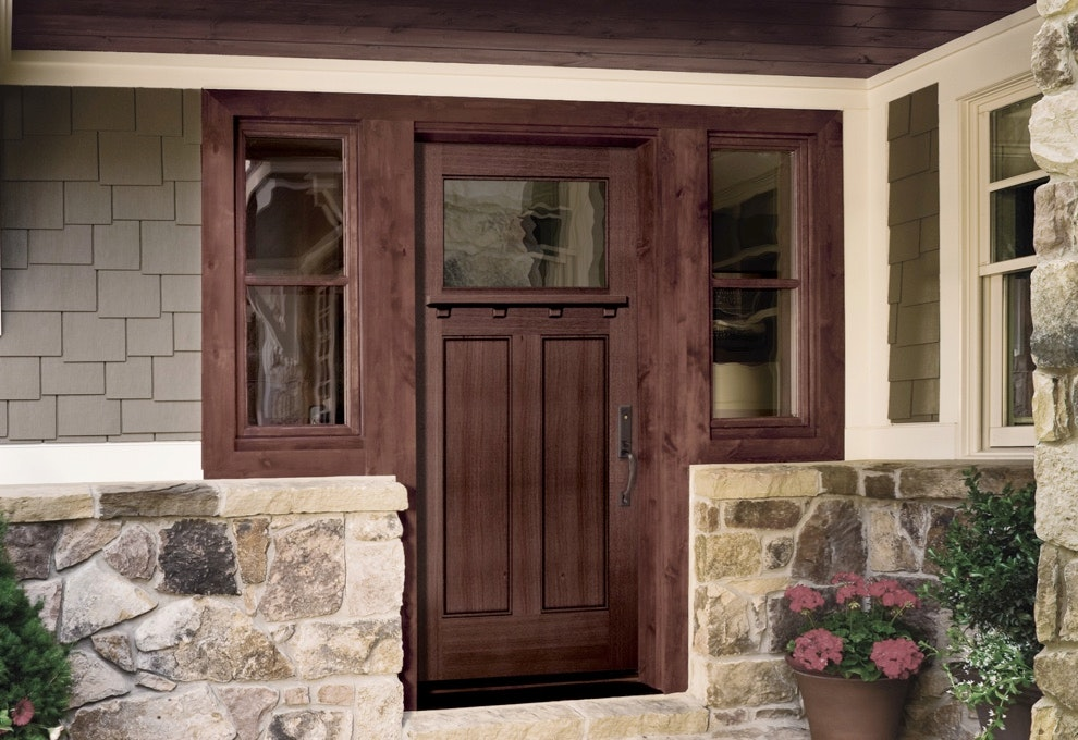 Two double-hung windows finished with a deep stain between a wood door with a large glass lite.