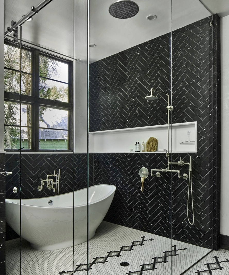 A modern shower with black subway tile and classic fixtures with two double-hung windows in the background.